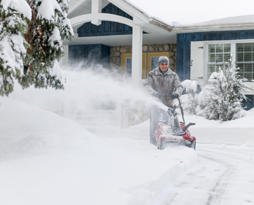 Man clearing driveway with snowblower